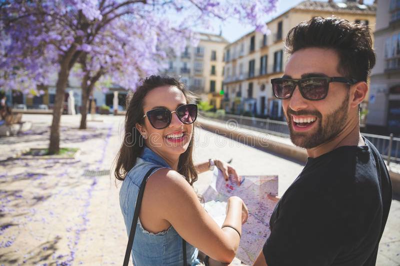 Pares felizes do turista na cidade que guarda o riso do mapa fotografia de stock