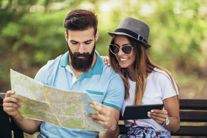 Pares felizes do turista que olham o mapa fotografia de stock royalty free