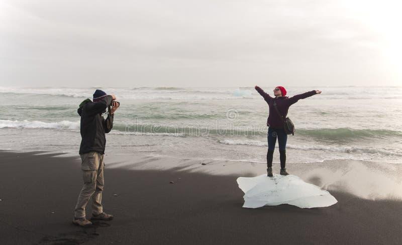 Pares felizes do turista que tomam uma foto na praia preta Islândia imagem de stock