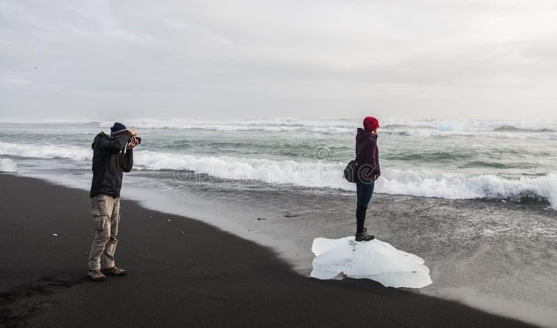 Pares felizes do turista que tomam uma foto na praia preta Islândia foto de stock