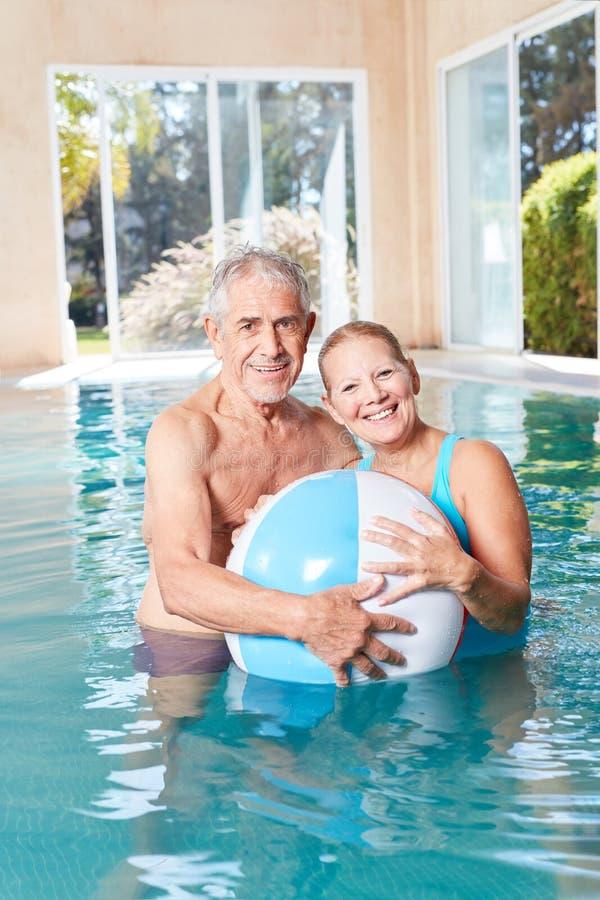 Pares felizes dos sêniores com uma bola de praia na piscina fotografia de stock