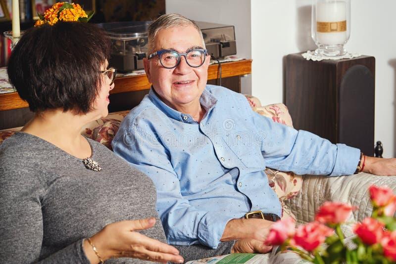 Pares felizes dos sêniores que sentam-se no sofá em casa fotos de stock