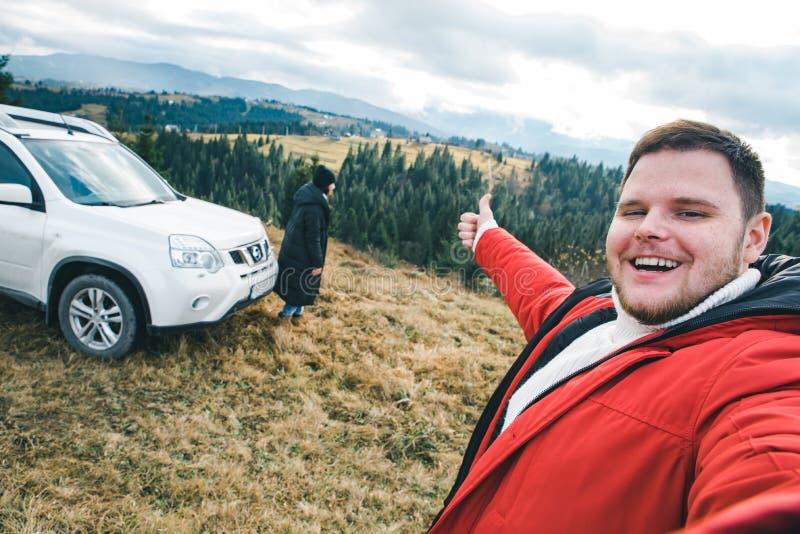 Pares felizes dos turistas no pico do monte com as montanhas bonitas no fundo Curso de carro fotografia de stock