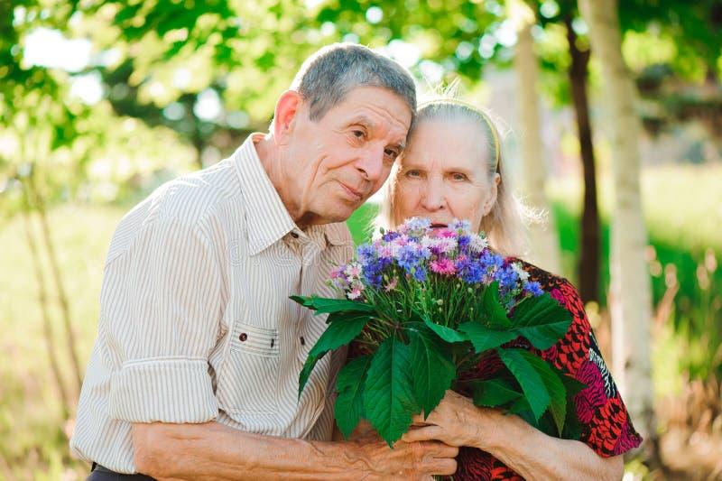 Pares felizes e muito velhos que sorriem em um parque em um dia ensolarado imagem de stock