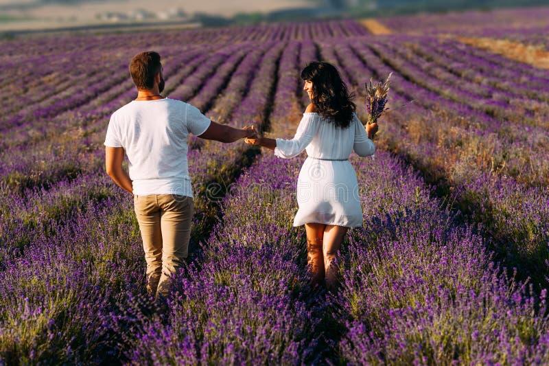 Pares felizes em campos da alfazema Homem e mulher nos campos de flor Viagem da lua de mel O par viaja o mundo Prados da alfazema foto de stock