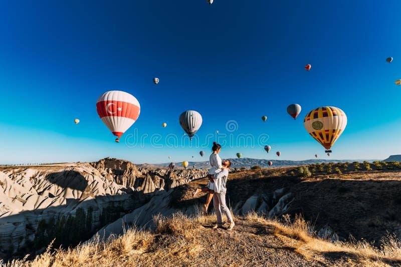 Pares felizes em Cappadocia O homem propôs à menina Lua de mel em Cappadocia Acople no festival do balão Viagem da lua de mel foto de stock