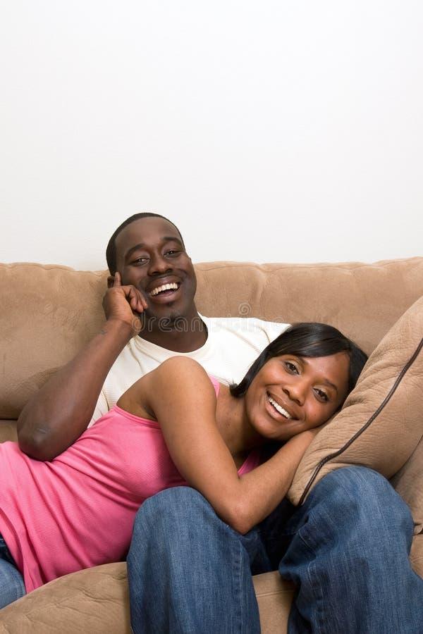 Pares felizes em sofá-Vertical imagens de stock royalty free