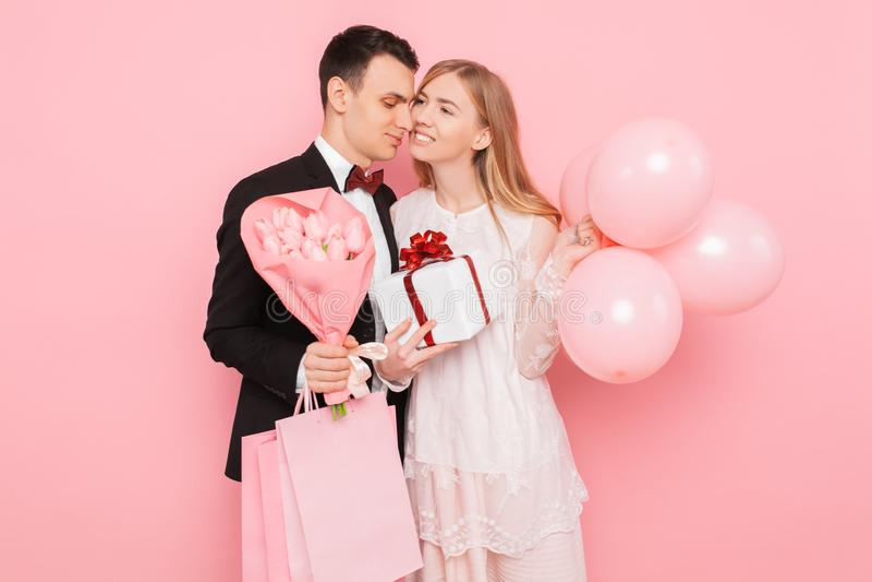 Pares felizes, homem e mulher, com um presente e um ramalhete das flores, com sacos, após a compra, em um fundo cor-de-rosa foto de stock royalty free