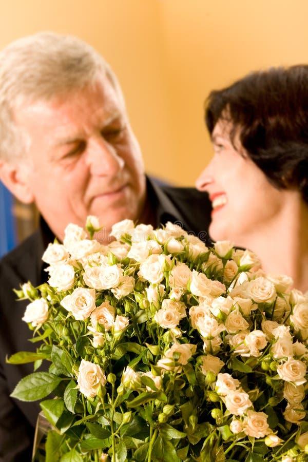 Pares felizes maduros com rosas fotografia de stock royalty free