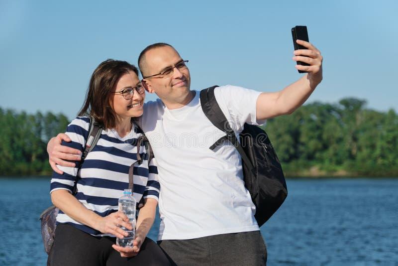 Pares felizes maduros que tomam a foto do selfie no telefone, pessoa que relaxa perto do rio no parque da noite do verão imagens de stock