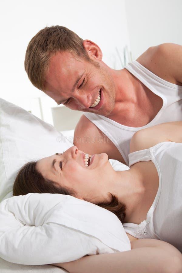 Pares felizes na cama ao lado de uma outros foto de stock royalty free