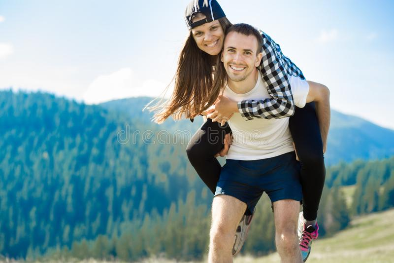 Pares felizes na caminhada do amor sobre montanhas O homem feliz novo guarda sua amiga foto de stock royalty free