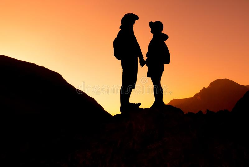Pares felizes na cordilheira no por do sol Fann Mountains fotos de stock