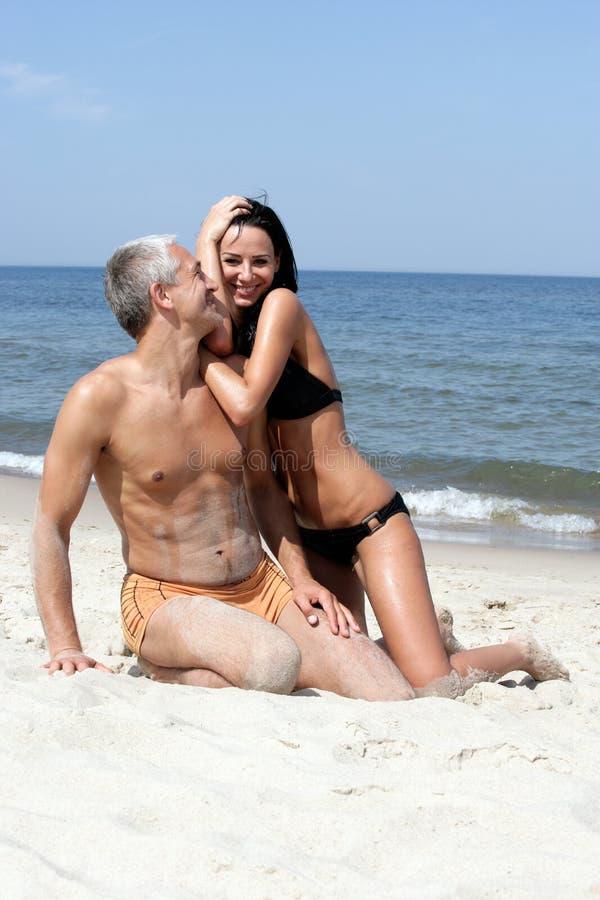 Pares felizes na praia imagens de stock