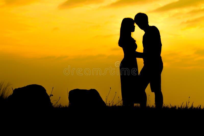 Pares felizes na rocha do por do sol - silhueta fotos de stock royalty free