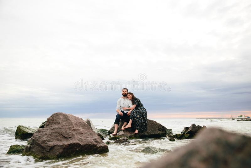 Pares felizes no amor que abraça na praia Assento nas rochas imagem de stock