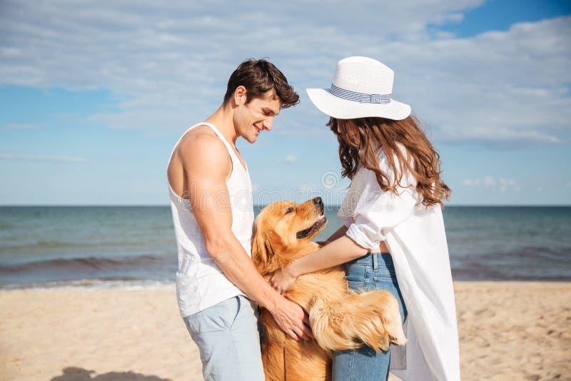 Pares felizes no amor que senta-se na praia com cão imagem de stock royalty free