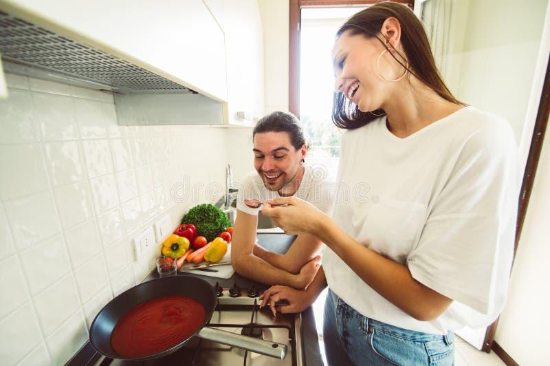 Pares felizes no amor que tem o divertimento que cozinha o togheter em casa fotografia de stock royalty free