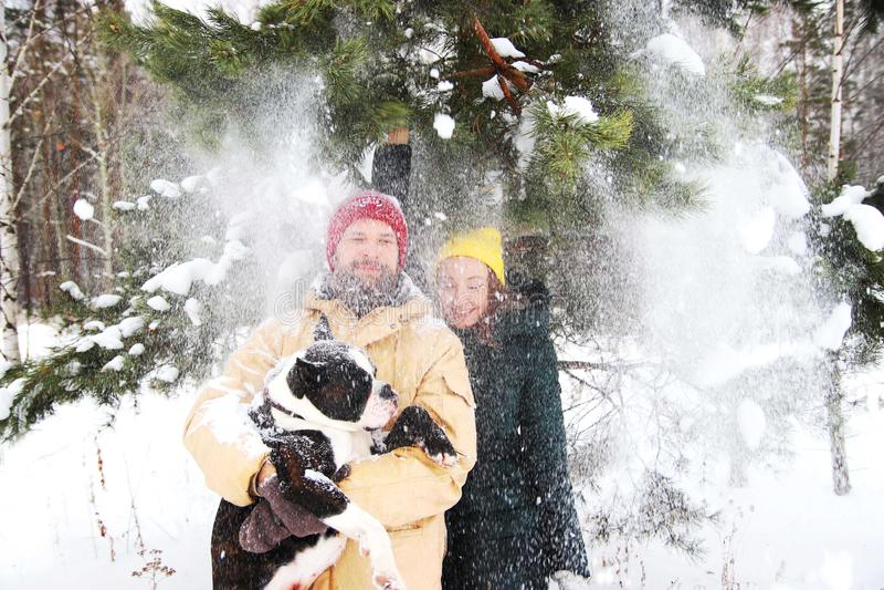 Pares felizes no amor que tem o divertimento na neve com seu cão do bebê fotografia de stock