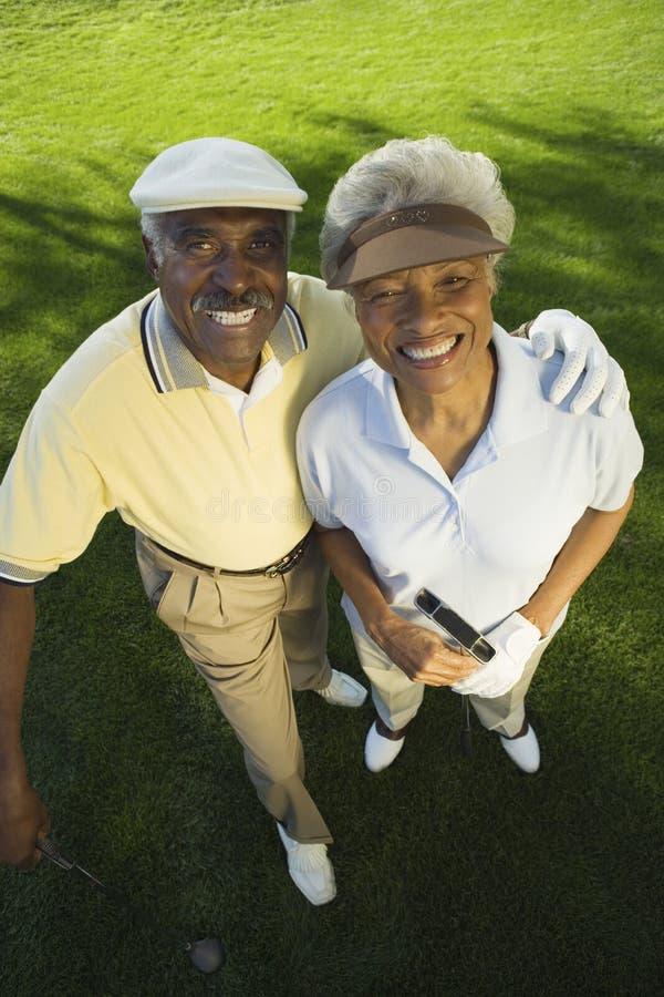 Pares felizes no campo de golfe imagens de stock royalty free
