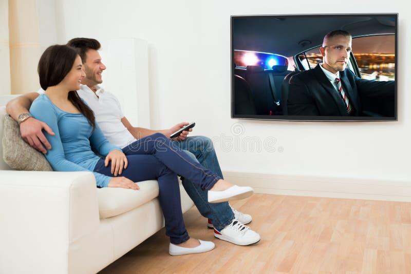Pares felizes no filme de observação da sala de visitas imagem de stock royalty free
