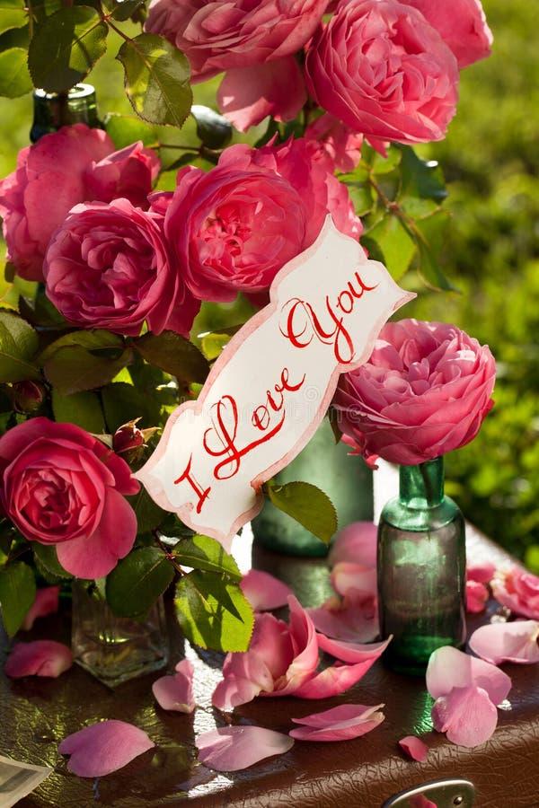 Pares felizes no fundo de rosas do jardim fotos de stock
