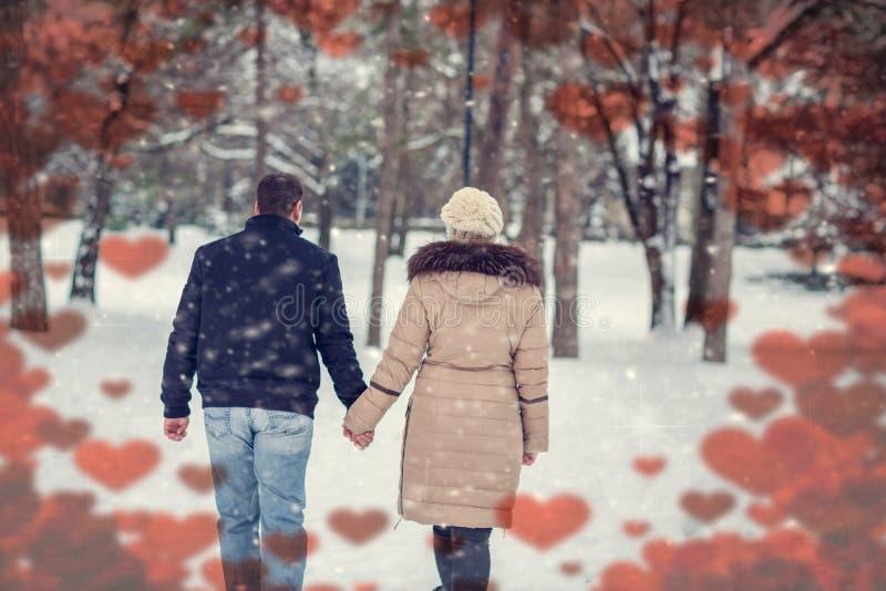 Pares felizes no parque do inverno que tem o divertimento no dia de Valentim fotos de stock