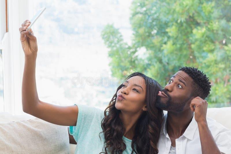 Pares felizes no sofá que toma o selfie fotografia de stock