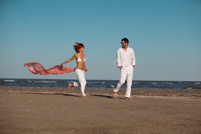 Pares felizes no vento do lenço da praia fotografia de stock
