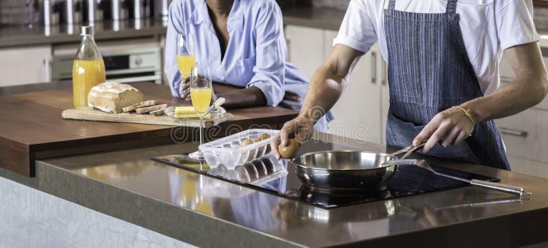 Pares felizes novos da raça misturada que preparam o café da manhã no cozimento da cozinha foto de stock royalty free