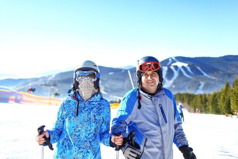 Pares felizes novos em montanhas nevado Férias do esporte de inverno Foco seletivo imagens de stock