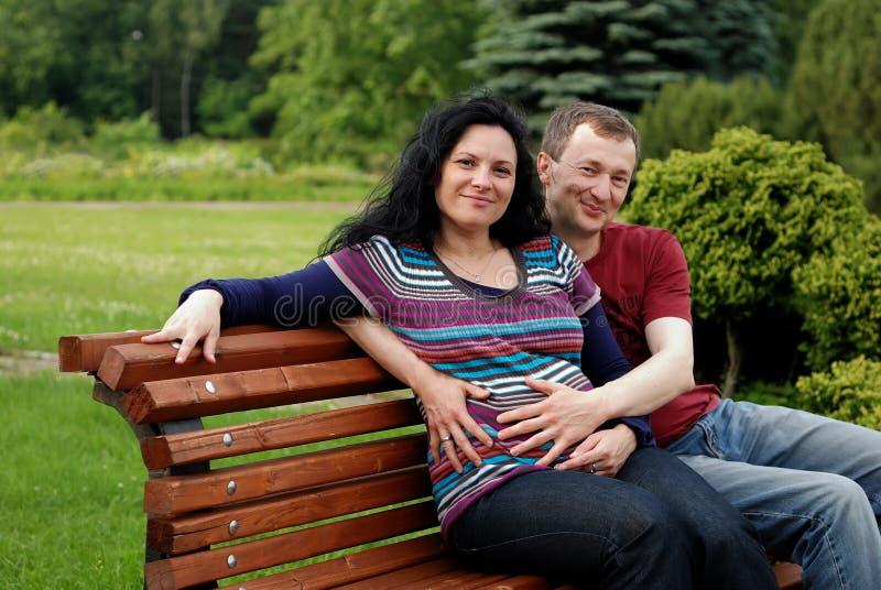 Pares felizes novos (mulher gravida) no banco fotografia de stock