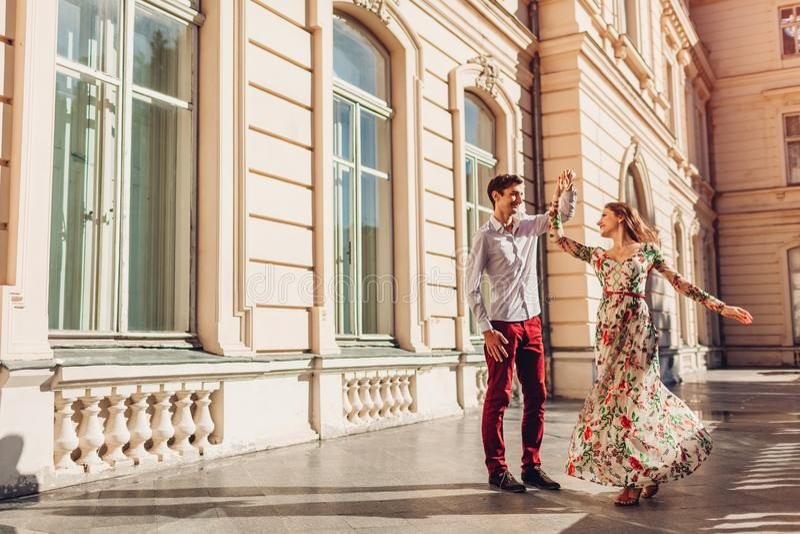 Pares felizes novos na dança do amor pelo palácio fora Homem e mulher que têm o divertimento na cidade fotos de stock
