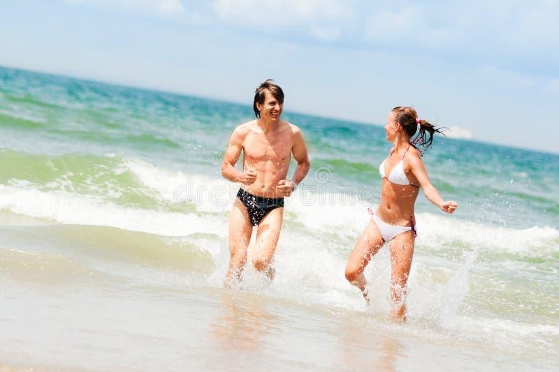 Pares felizes novos na praia imagens de stock royalty free
