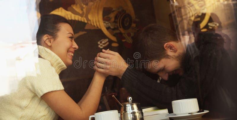 Pares felizes novos no café, vista através de uma janela imagens de stock royalty free