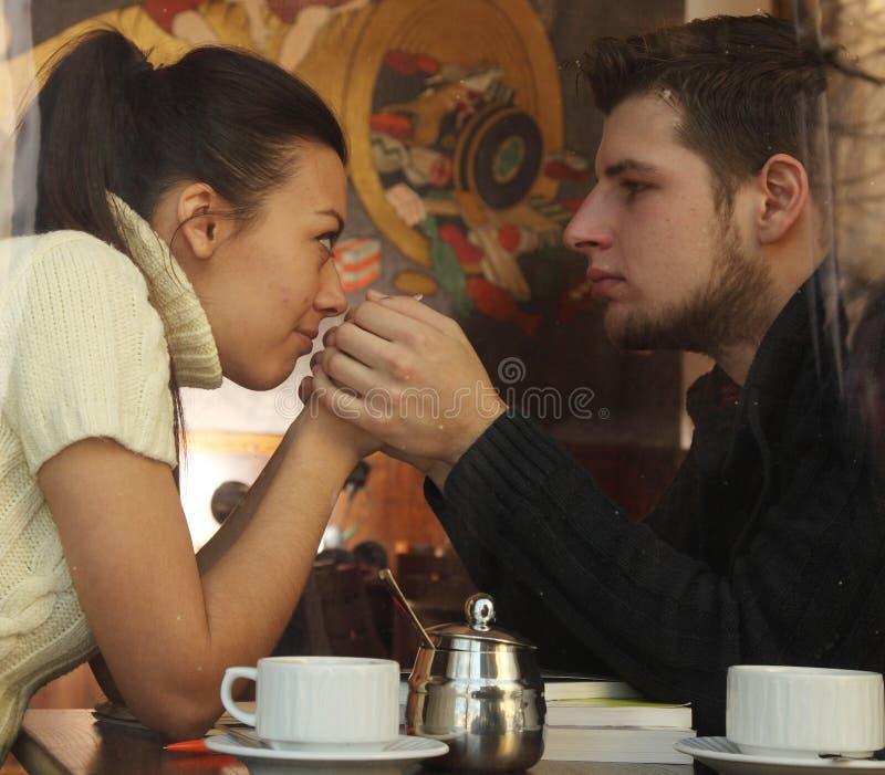 Pares felizes novos no café, vista através de uma janela fotos de stock royalty free