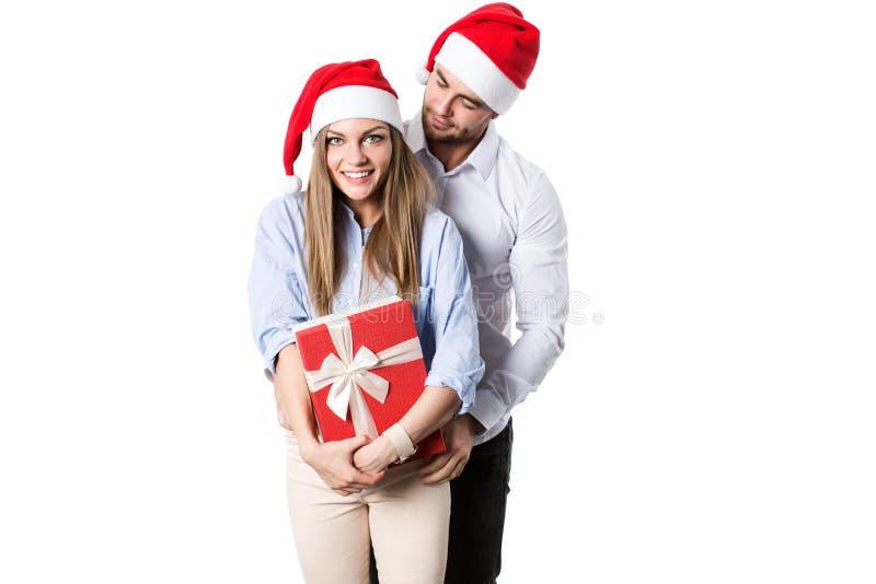 Pares felizes novos no chapéu de Santa com caixas de presente fotos de stock royalty free