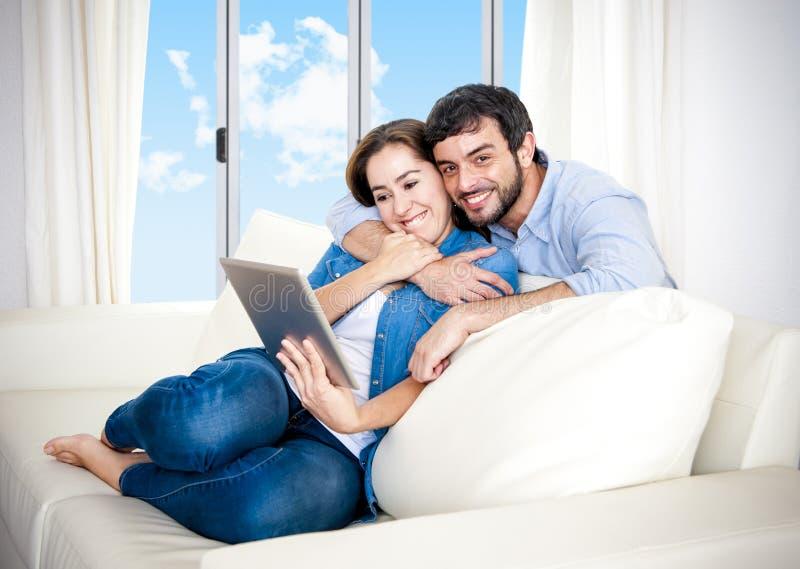 Pares felizes novos no sofá em casa que aprecia usando a tabuleta digital fotografia de stock