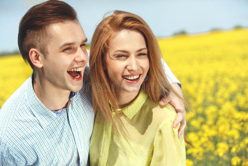 Pares felizes novos que abraçam e que riem fotos de stock royalty free