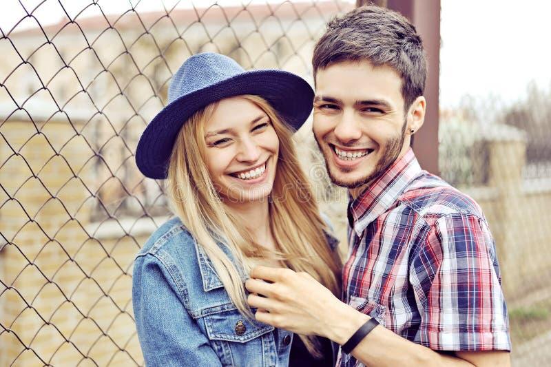 Pares felizes novos que abraçam e que riem foto de stock royalty free