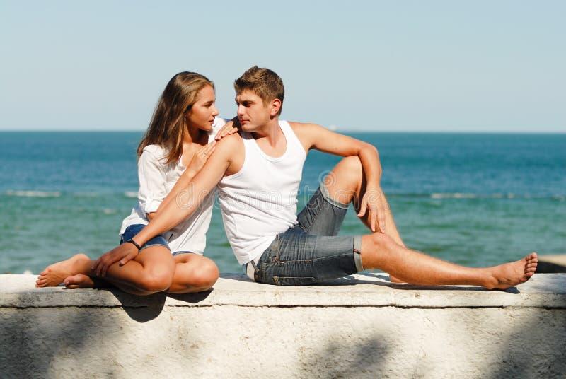 Pares felizes novos que abraçam na costa de mar fotografia de stock royalty free