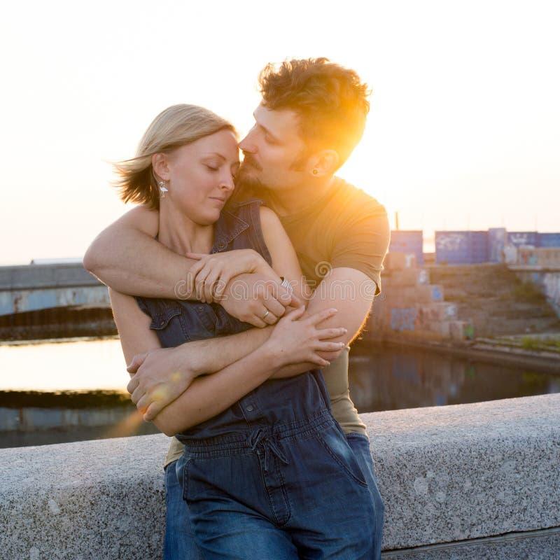 Pares felizes novos que abraçam na luz do por do sol fotografia de stock