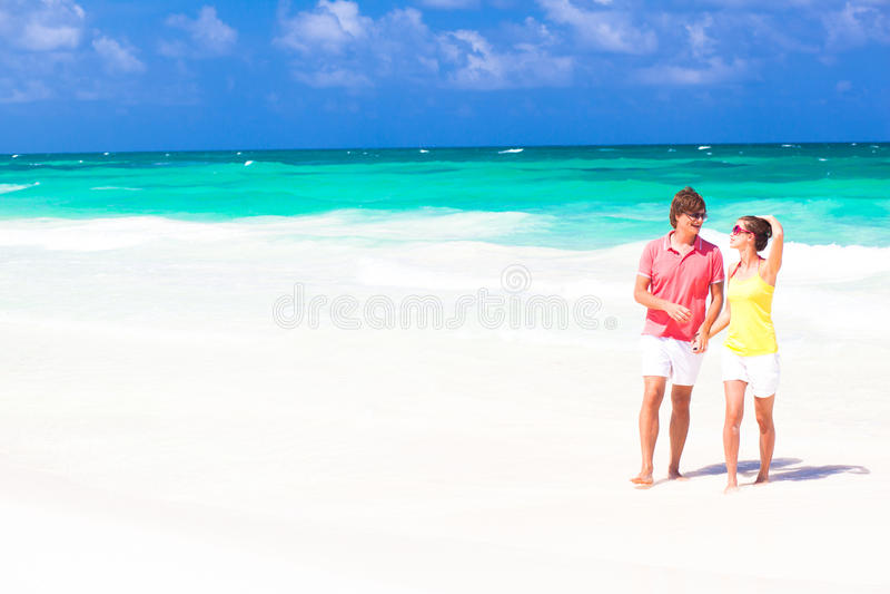 Pares felizes novos que andam no sorriso da praia. fotos de stock