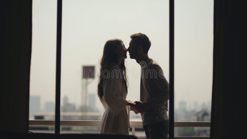 Pares felizes novos que beijam e que apreciam a vista de uma cidade de negligência do balcão na manhã durante a lua de mel fotos de stock