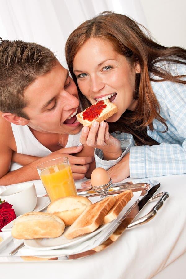 Pares felizes novos que comem o pequeno almoço luxuoso fotos de stock