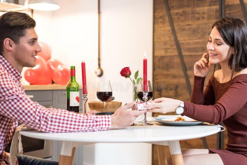 Pares felizes novos que comemoram o dia do ` s do Valentim com um jantar em casa fotografia de stock royalty free