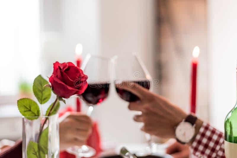 Pares felizes novos que comemoram o dia do ` s do Valentim com um jantar em casa que brinda com vinho foto de stock royalty free