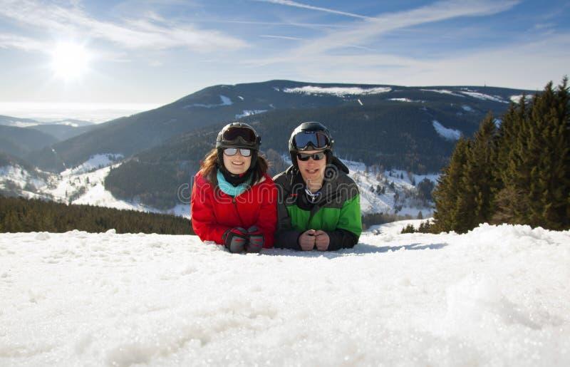 Pares felizes novos que encontram-se em montanhas nevado. Férias do esporte de inverno fotografia de stock
