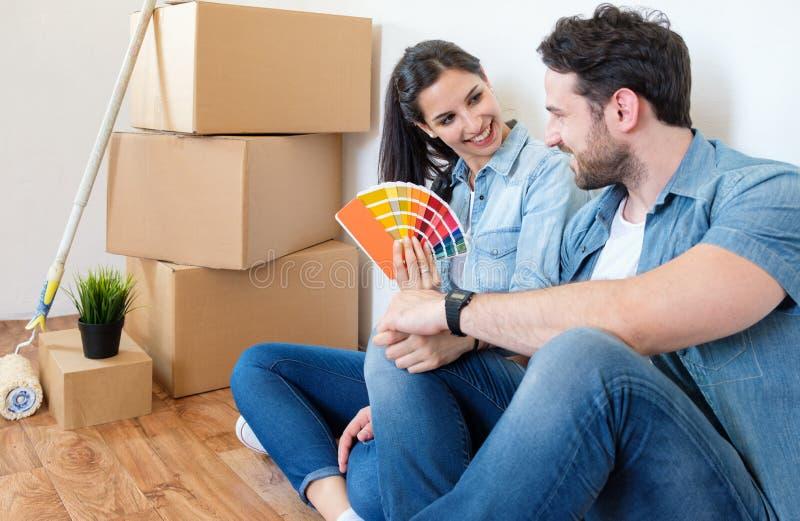 Pares felizes novos que escolhem cores para pintar sua casa e ter uma ruptura fotografia de stock