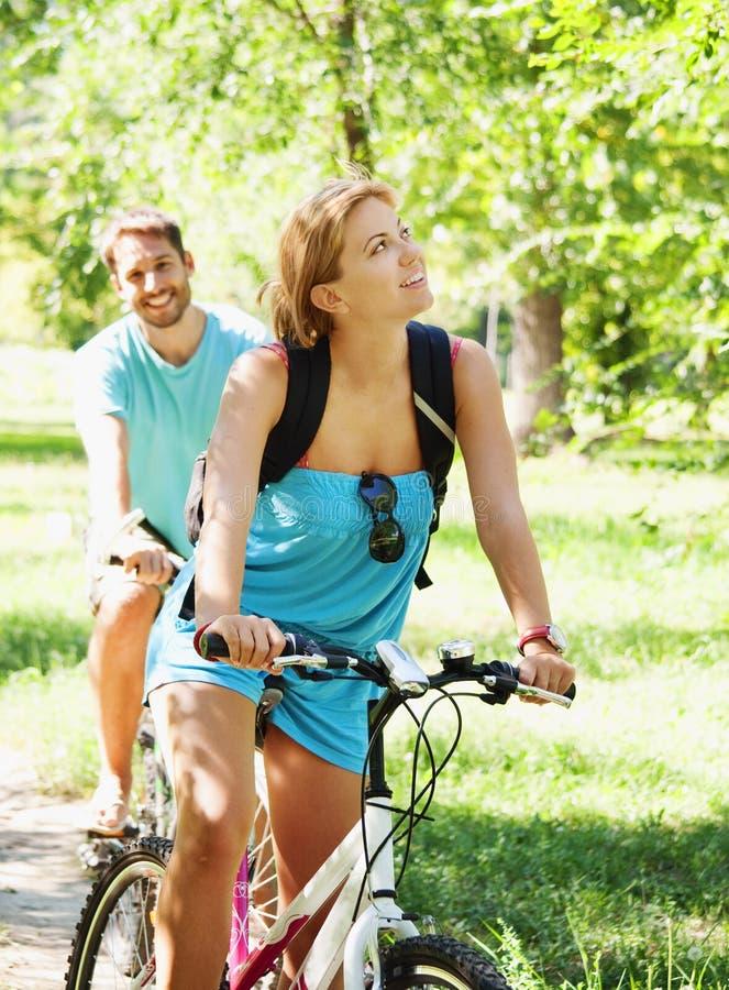Pares felizes novos que montam uma bicicleta imagem de stock